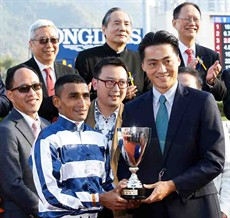 Mr. Oscar Chow Vee Tsung, Non-Executive Director of Chevalier International Holdings Limited, presents a replica trophy to winning jockey Karis Teetan